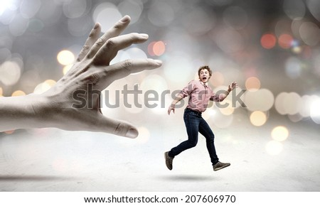 Young man trying to run away from big male hand - stock photo