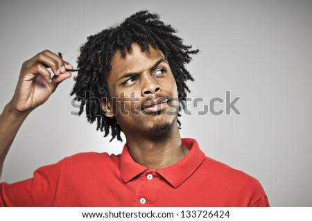 Young Man Twists His Hair While Plotting - stock photo