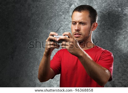 young man typing on mobile phone against a grunge wall - stock photo