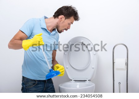 Young man unclogging a stinky toilet with plunger, isolated on white background. - stock photo