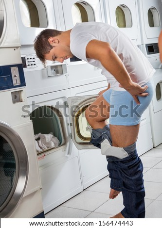 Young man undressing his clothes in front of washing machine at laundry
