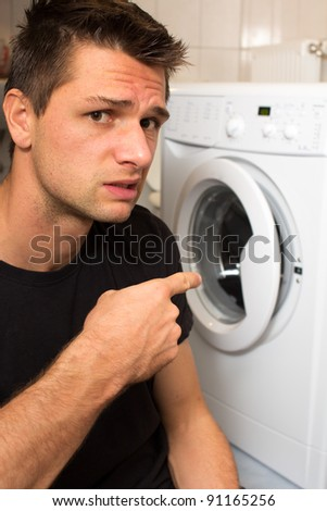 Young Man Unhappy With Washing Machine - stock photo