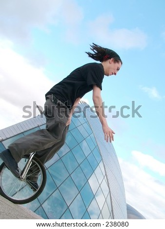 Young man unicycling quickly with modern building in the background.