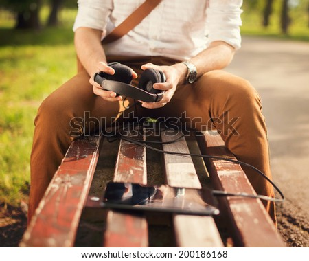 Young man used a digital tablet outdoors and holding headphones in hands - stock photo