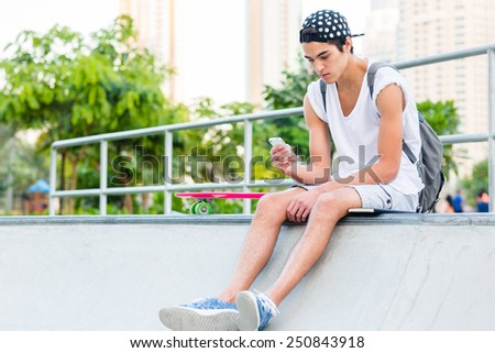 Young man using a cellphone while sitting at the skatepark. - stock photo