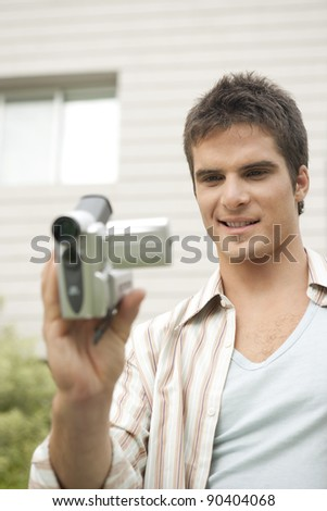 Young man using a digital video camera in office garden.