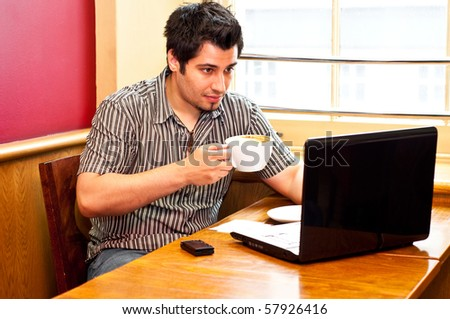 young man using a laptop and drinking cappuccino - stock photo