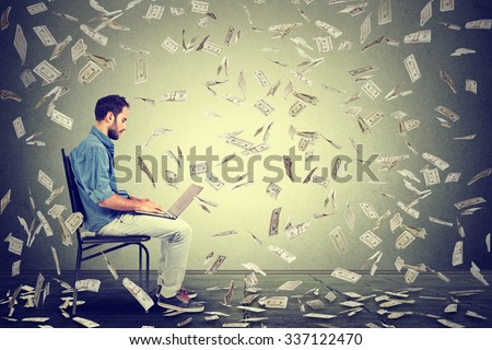 Young man using a laptop building online business making money dollar bills cash falling down. Money rain beginner IT entrepreneur success economy concept  - stock photo