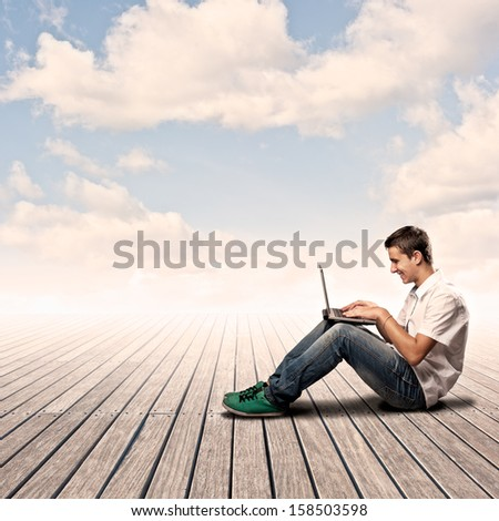 young man using a laptop on a wharf - stock photo