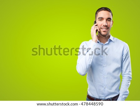 Young man using a mobile phone on green background