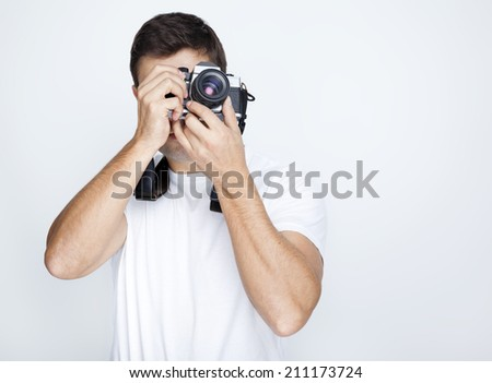 Young man using a retro camera against gray background - stock photo