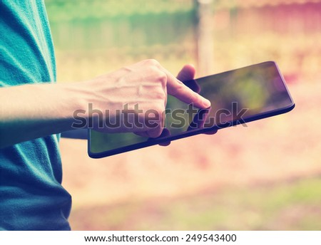 Young man using a tablet device outside - stock photo