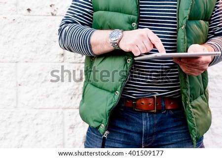Young man using a tablet, Dressed casually. Jeans, Vest. Bright crisp post processed. Urban life style, technology, online, business, shopping, fashion and job hunting concept.
