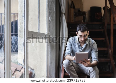 Young man using a tablet on the stairs in the office - stock photo