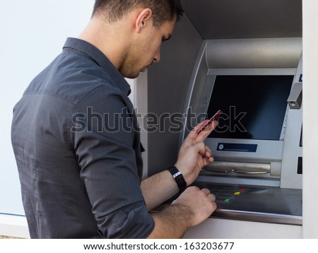 Young man using ATM