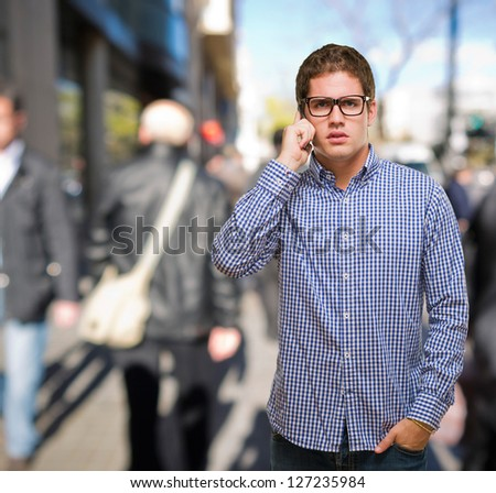 Young Man Using Cell Phone against a street background - stock photo