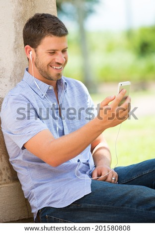 Young man using cell phone and head phones outside - stock photo