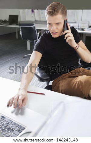 Young man using cell phone and laptop at desk in office - stock photo