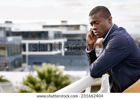 Young man using cell phone mobile technology to communicate with work in urban city - stock photo