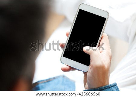 Young man using cell phone, shallow depth of field