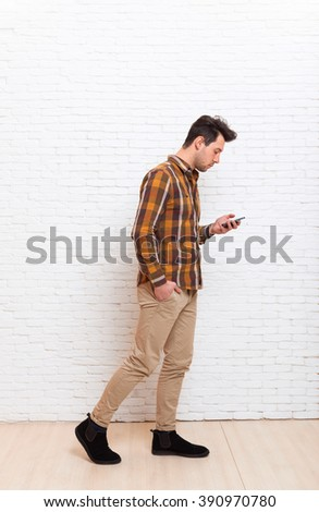 Young Man Using Cell Phone Smartphone Busy Walking Social Network Communication Full Length Over White Brick Office Wall - stock photo
