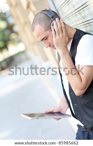 Young man using electronic tablet in the street