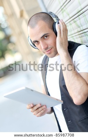 Young man using electronic tablet in the street - stock photo