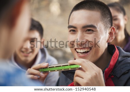 Young man using harmonica, portrait - stock photo