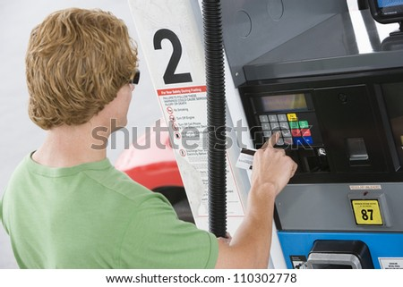 Young man using his debit card to pay for gasoline - stock photo
