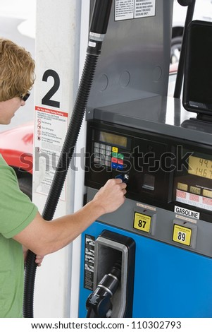 Young man using his debit card to pay for gasoline