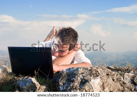 Young man using his laptop, lying on the  rock