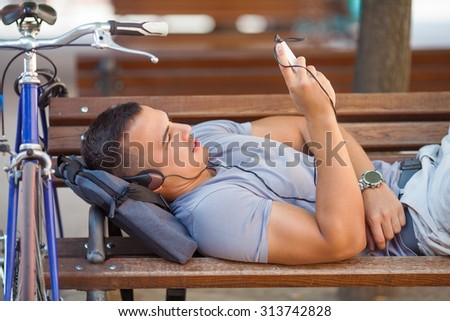 Young man using his mobile phone while taking a break in the city with his bicycle beside him - stock photo