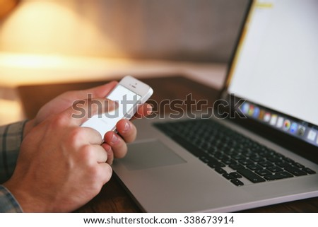 Young man using his phone and laptop, close up - stock photo