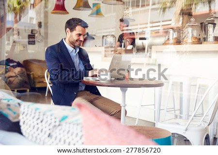 Young man using laptop at a cafe - stock photo