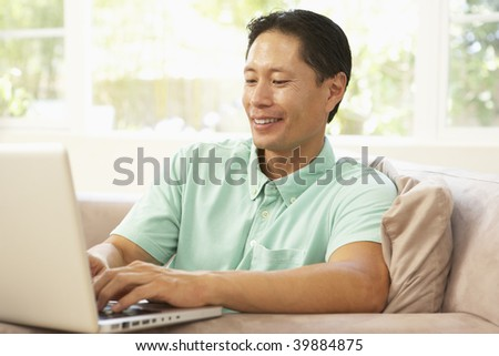 Young Man Using Laptop At Home - stock photo