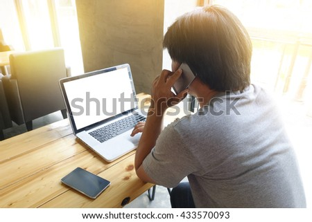 young man using laptop computer with blank copy space screen and calling mobile phone while sitting in cafe,flare sun