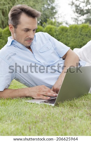 Young man using laptop in park - stock photo