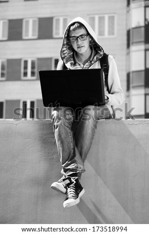 Young man using laptop outdoor - stock photo