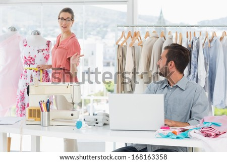 Young man using laptop with female fashion designer working in background at the studio