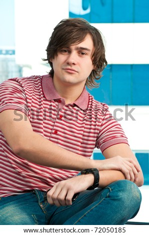young man using mobile phone, looking at camera - stock photo