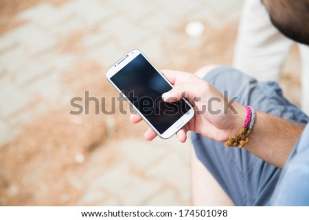 Young man using mobile smart phone - stock photo