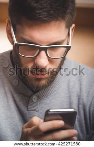 Young man using phone in office - stock photo