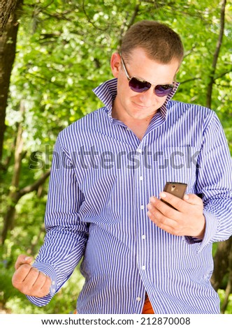 Young man using phone while walking through the green forest - stock photo