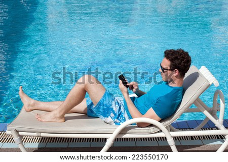 young man using smartphone near the pool in luxury hotel - stock photo