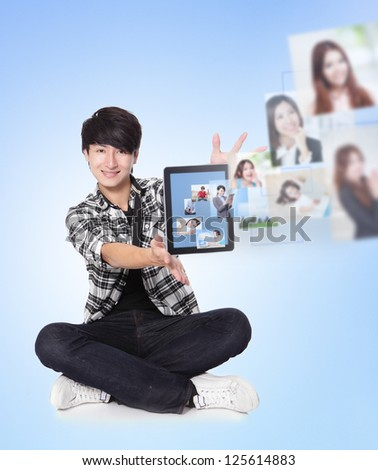 Young man using social networking with friends. Portrait of handsome guy using his tablet pc looking at camera and smiling. blue background, asian model