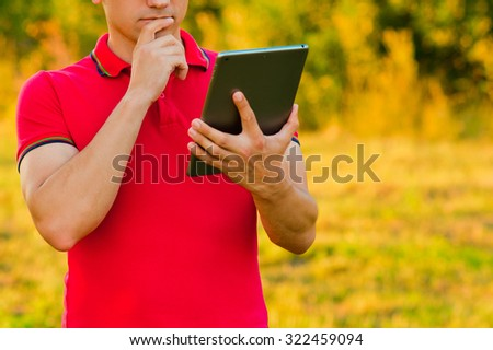 Young man using tablet computer on autumn city park. Man thinking about something outdoors in the park - stock photo