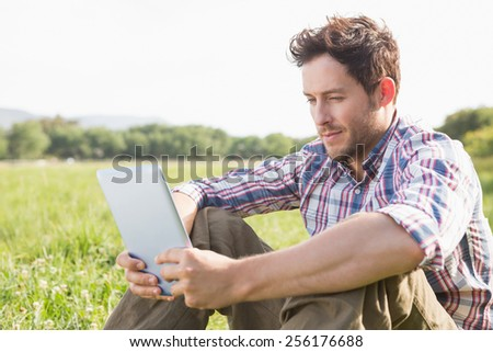 Young man using tablet in the countryside on a sunny day - stock photo
