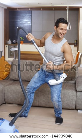 Young man using vacuum cleaner as guitar, having fun in living room.