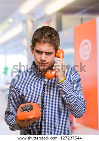 Young Man Using Vintage Telephone at a mall - stock photo
