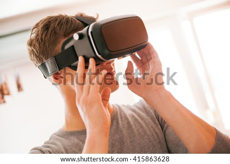 Young Man Using VR In The Living Room - stock photo